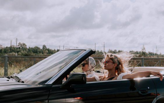 Dame sidder i bil med vind i håret